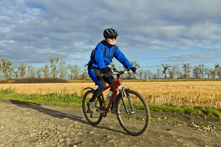 Woman riding mountain bike in autumn photo