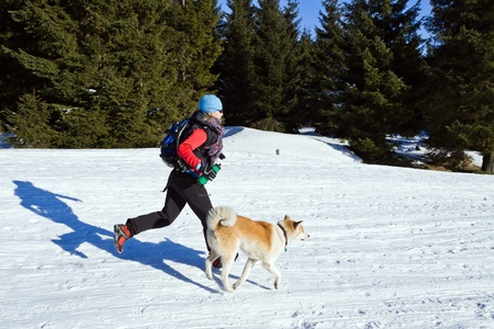 Young woman running with an Akita dog in winter mountains