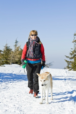 Young woman hiking in winter mountains with akita dog photo