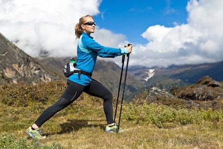 Joven mujer se extiende y nordic walking en las montañas del Himalaya en Nepal