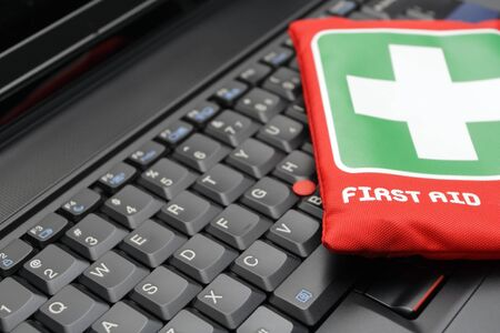 Closeup of black laptop with first aid kit on a keyboard. photo