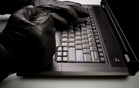 thieves: Security concept with mad hacker working on laptop at night