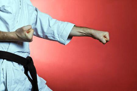 martial arts: Hombre joven practicando karate sobre fondo rojo