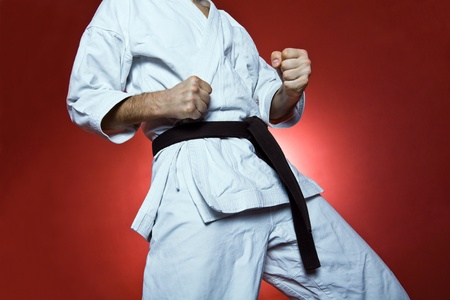 Young man practicing karate over red background photo