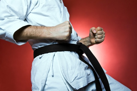 Young man practicing karate over red background (karate,\ judo)