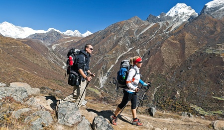 Young couple hiking in himalayas mountains in Nepal photo