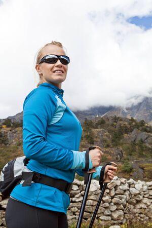 Young woman hiker hiking in Himalaya Mountains in Nepal photo