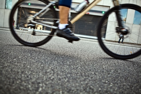 Man riding a bike on city street, motion blur and selective focus photo