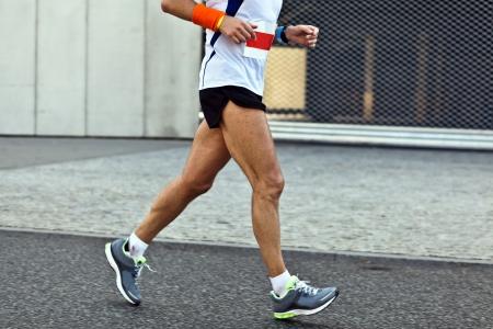 Man running in marathon on city street, motion blur