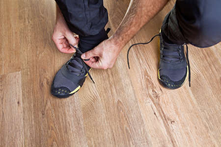 Man tying trail running shoes, ready to workout photo