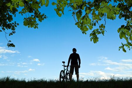 Mountain biker silhouette in summer nature photo
