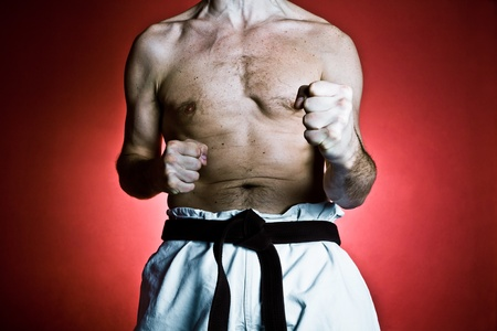 mixed martial arts: Young man practicing karate over red background