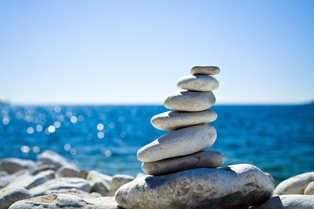 Pebble Beach: Close-up of white pebbles stack over blue sea Stock Photo