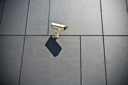 Security camera on gray modern building wall, technology in city photo