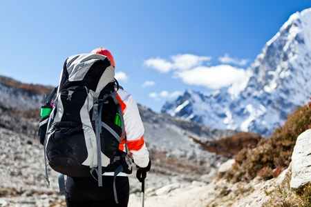 Young woman hiker hiking in Himalaya Mountains in Nepal. Focus on a backpack. photo