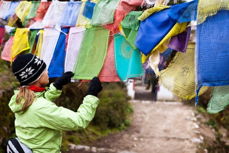 Woman reading prayers flag in Nepal, Thyangboche Monastery  Tengboche Himalayan village in the Khumbu region of northeastern Nepal, located at 3867 meters  12687 ft  photo
