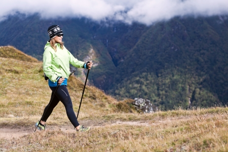 walking pole: Young woman nordic walking in mountains, fitness and exercise outdoors  Stock Photo