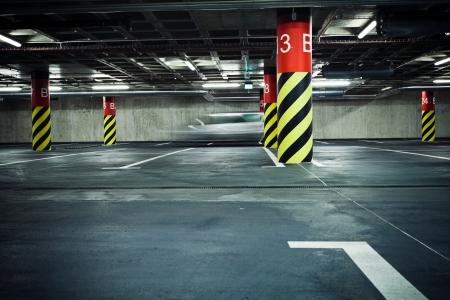 parking lot interior: Parking garage underground interior, blurred car passing by