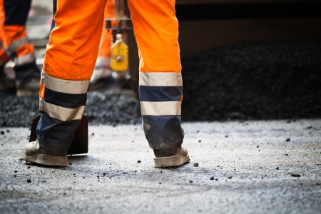 Workers on a road construction, industry and teamwork, new asphalt Stock Photo