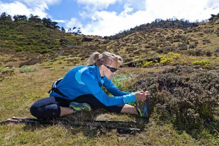 Young woman exercising and stretching in mountains, nordic walking in summer photo