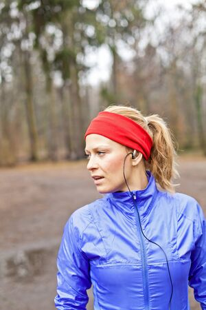 Woman runner exercising in winter forest photo