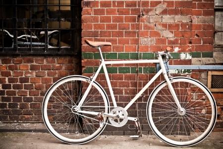 clavados: Ciudad bicicleta de artes fijos y pared de ladrillo rojo