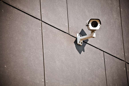 White security camera on office building, safety system photo