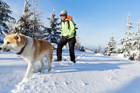 Woman hiking in winter mountains with akita dog Stock Photo