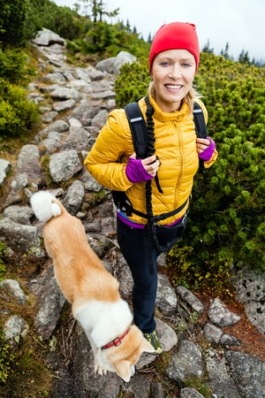Woman hiking in mountains with akita dog, Karkonosze Mountain Range Poland. Sport, activity and recreation in autumn. Fitness and exercising in nature. photo