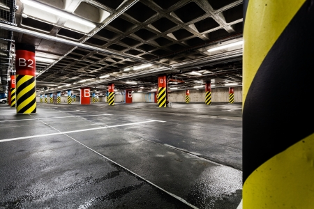 Parking garage underground interior. Bright neon light in industrial building basement, steel and concrete.