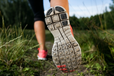 woman run: Walking or running shoes in forest, adventure and exercising in summer nature