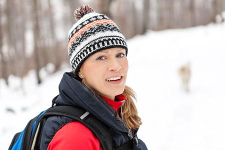 Woman hiking in white winter forest. Recreation and healthy\ lifestyle outdoors in nature. Beauty blond looking at camera on\ sunset.
