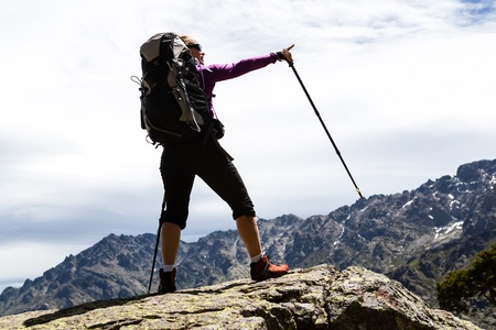 mountaineer: Woman hiking with backpack in mountains, silhouette Stock Photo
