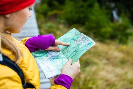 Woman hiking and reading map in forest, Karkonosze Mountains in Poland