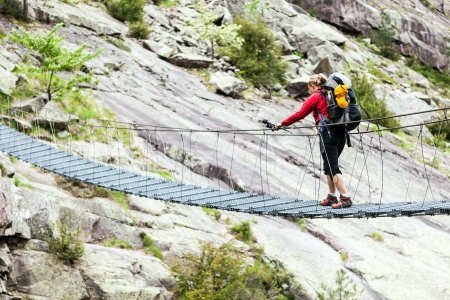 trekker: Woman hiking with backpack in mountains, crossing steel suspension bridge