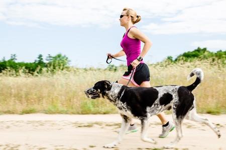 Corredor Mujer corriendo con el perro en el camino rural en la naturaleza de verano, gimnasio y ejercicio al aire libre, el desenfoque de movimiento. Foto de archivo