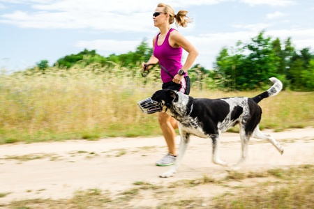 girl jogging: Woman runner running with dog on country road in summer nature, fitness and exercising outdoors, motion blur.