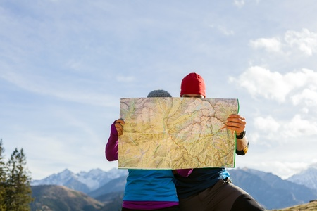 Man and woman hikers hiking in mountains. Young couple looking at map and planning trip or get lost. Selective focus on a map photo