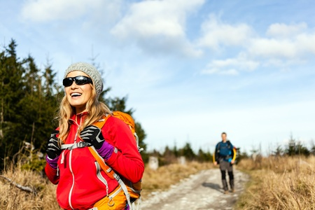 Man and woman hikers hiking on mountain trail autumn or winter nature. Young couple backpackers walking in forest, Poland. Stock Photo