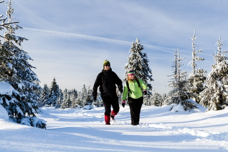 Man and woman hikers walking in winter mountains. Young couple happy walking no white snow in mountain forest, Poland photo