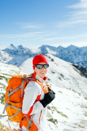 Hiking and walking woman, success and freedom in mountains. Fitness and healthy lifestyle outdoors in winter nature. Female mountaineer, climber on mountain ridge in Tatras, Poland. photo