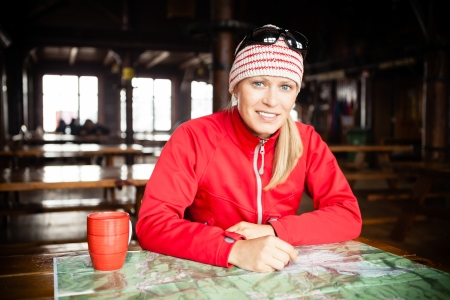 hostel: Woman hiker with map planning trip, inside cold shelter or hostel in winter