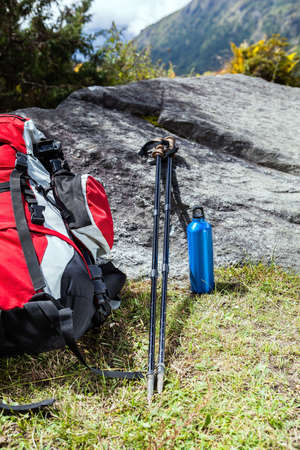 trekking pole: Hiking equipment in mountains, sticks, water bottle and backpack on a rock, green grass, outdoors in autumn nature.