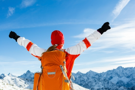Hiking woman and success in mountains. Fitness and healthy lifestyle outdoors in winter nature Stock Photo
