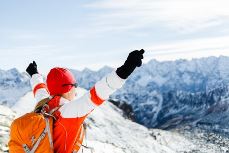 trekker: Hiking woman and success in winter mountains. Fitness and healthy lifestyle outdoors in snowy nature. Female mountaineer or climber on top of mountain peak happy with arms raised. Stock Photo