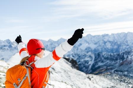 Senderismo mujer y el éxito en las montañas de invierno. Salud y estilo de vida saludable al aire libre en la naturaleza nevado. Mujer alpinista o escalador en la cima del pico de montaña feliz con los brazos levantados. Foto de archivo