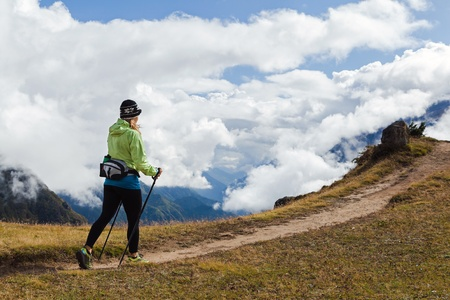 Woman hiker nordic walking in Himalaya Mountains in Nepal. Trekking in autumn nature, beautiful mountain landscape.