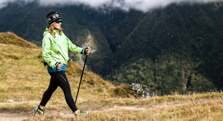 Woman hiker nordic walking in Himalaya Mountains in Nepal. Exercising in autumn nature photo