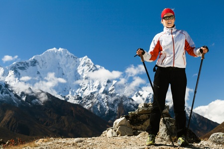 Woman hiker hiking in Himalaya Mountains in Nepal. Young female nordic walking in high mountain, success and achievement outdoors in nature. Adventure trekking in Asia. photo