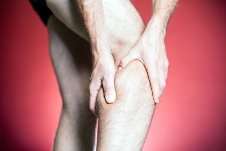 cramp: Knee Pain, man holding leg, making massage with hands. Physical injury and recovery or rehabilitation concept.